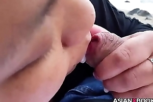 Asian babe gives outdoor blowjob
